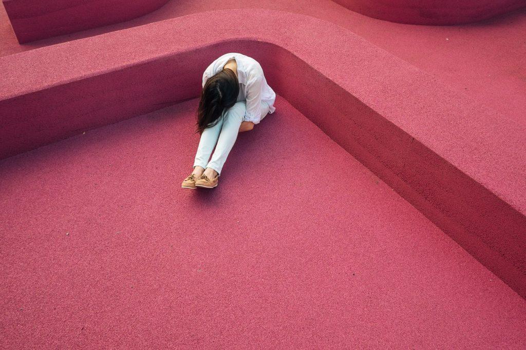 ピンクの床で悩む女性