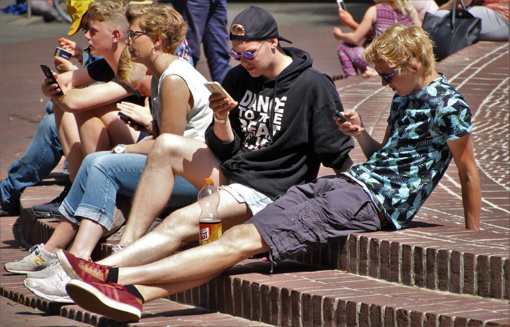 スマホを見る若者たち