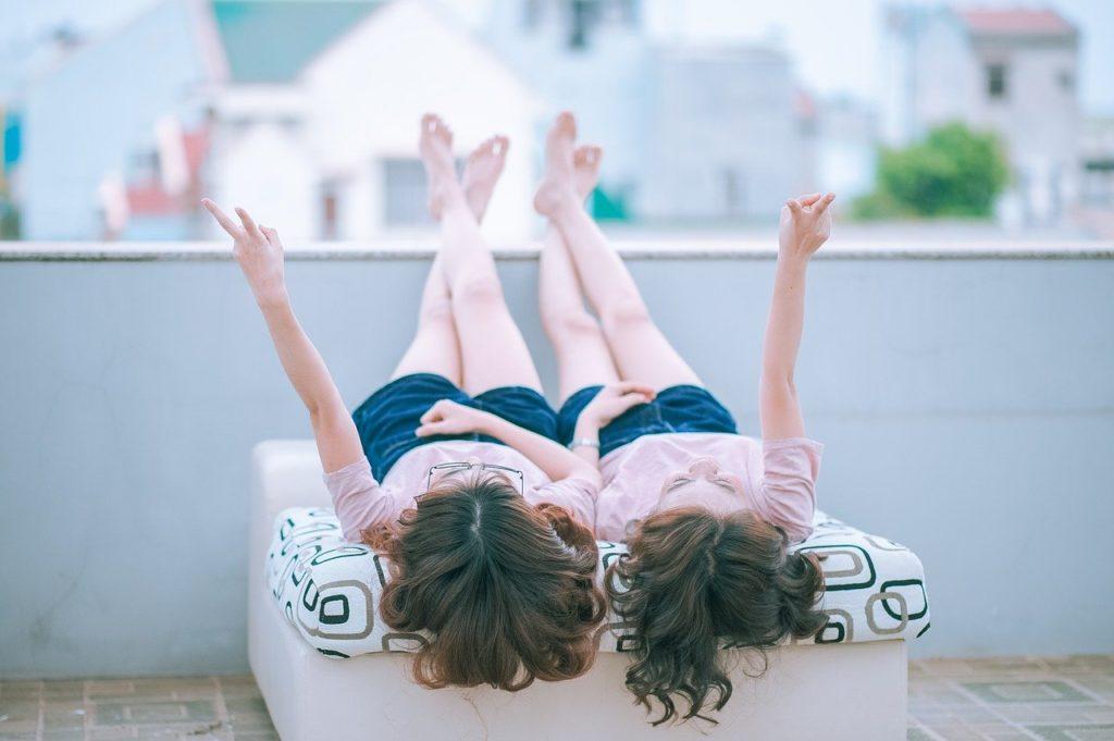 二人の女性がベッドに横たわっているところ
