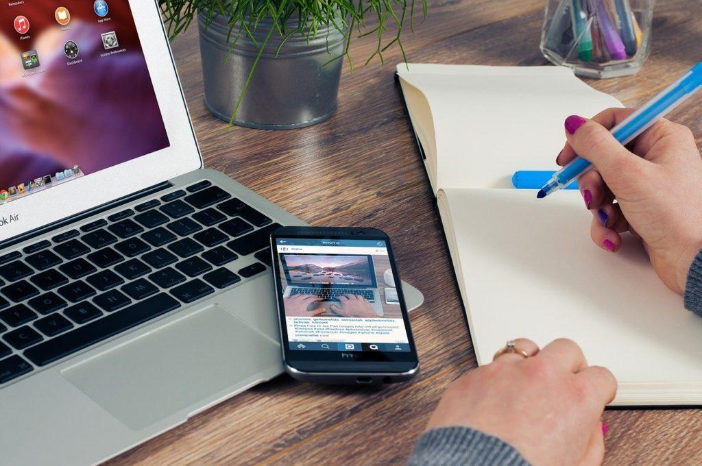 パソコンとノートで作業する女性