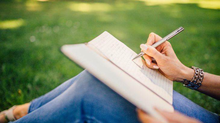 女性がノートに書き込んでいる