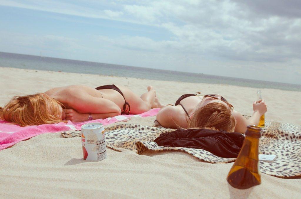 海辺に寝転がる女性たち