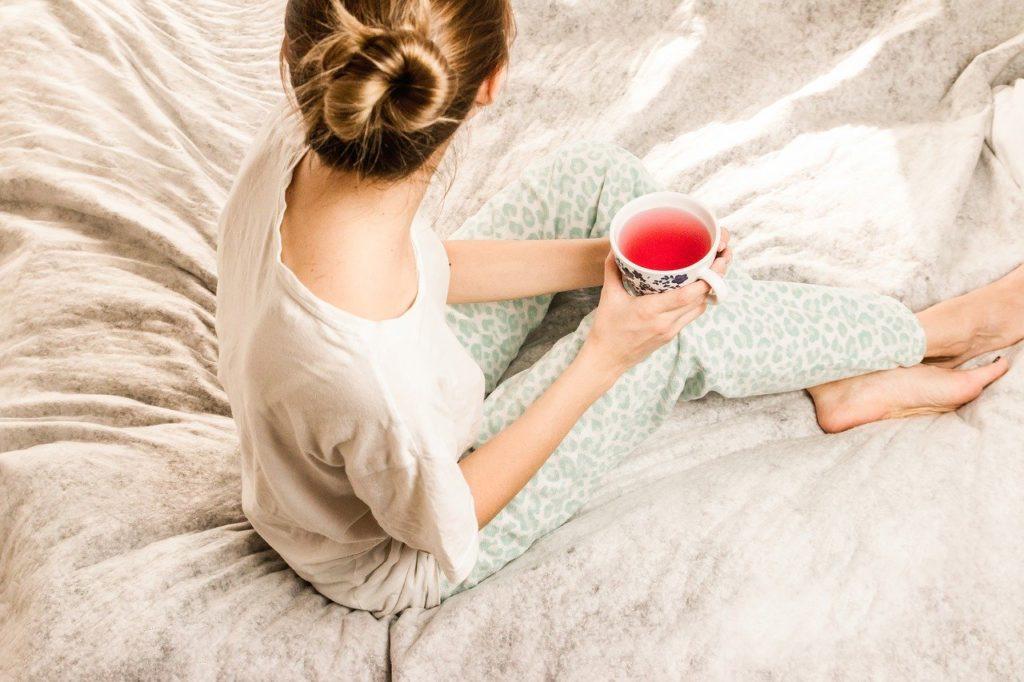 ベッドの上でお茶を飲む女性