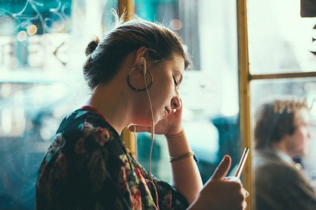 窓辺でスマホを操作する女性