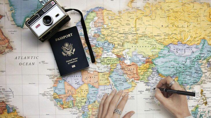地図とパスポート 旅行の計画を立てる女性
