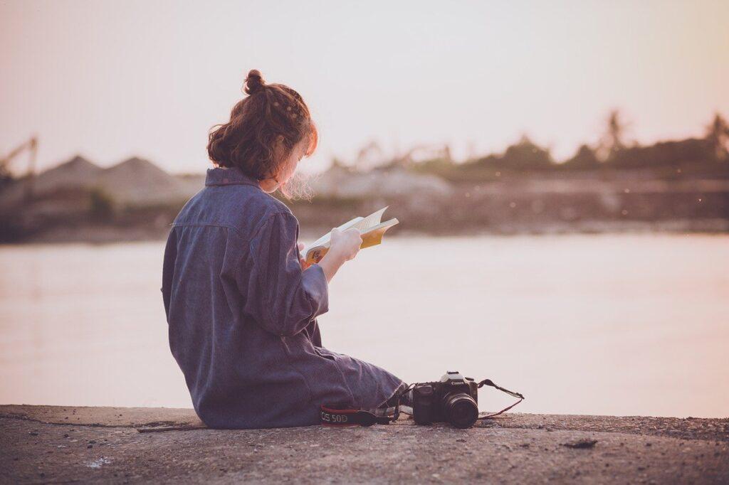 川辺で本を読む女性